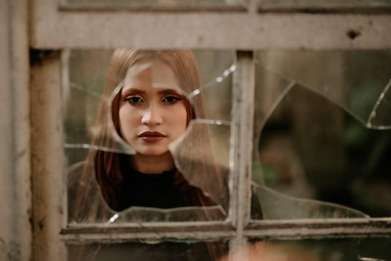 Eine traurige Frau steht vor einer kaputten Tür