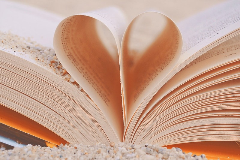 Buchblätter in Herzform gefaltet und Sand auf dem Buch