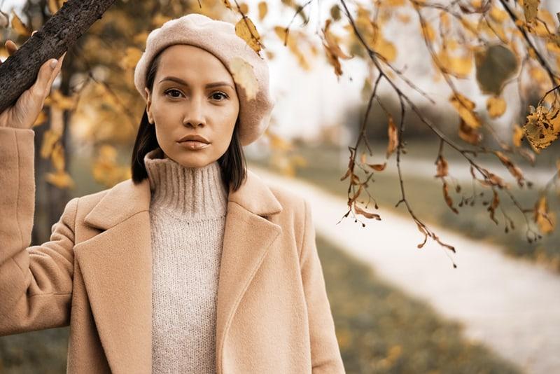 Dame im beige Mantel allein stehend unter dem Baum
