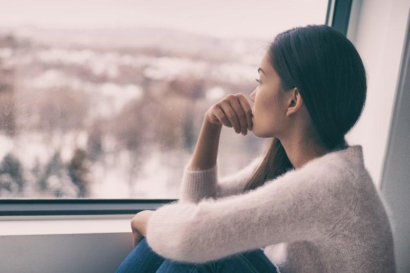 Das Mädchen beobachtet die schneebedeckte Idylle durch das Fenster
