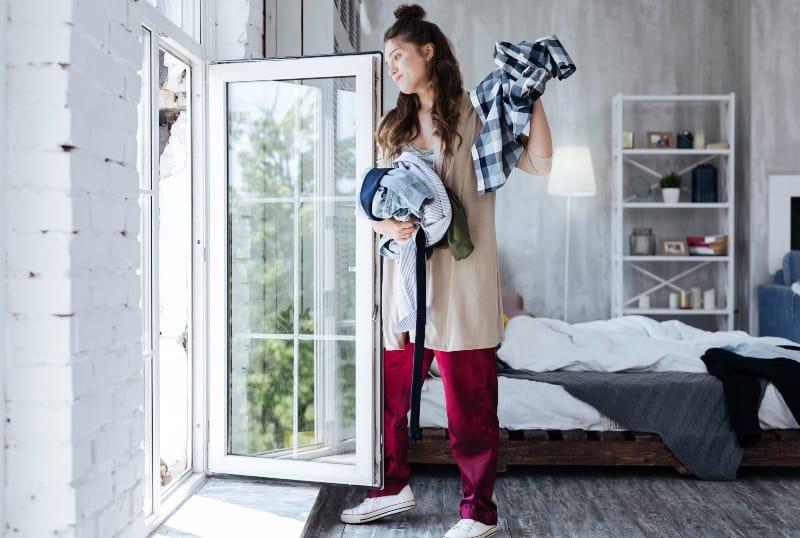Das Mädchen wirft ihre Kleider aus dem Fenster