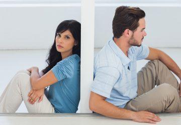 Ein Mann und eine Frau lehnen sich an die Wand zwischen ihnen