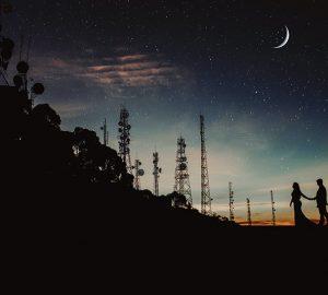 ein Paar Händchen haltend und unter dem Sternenhimmel spazieren