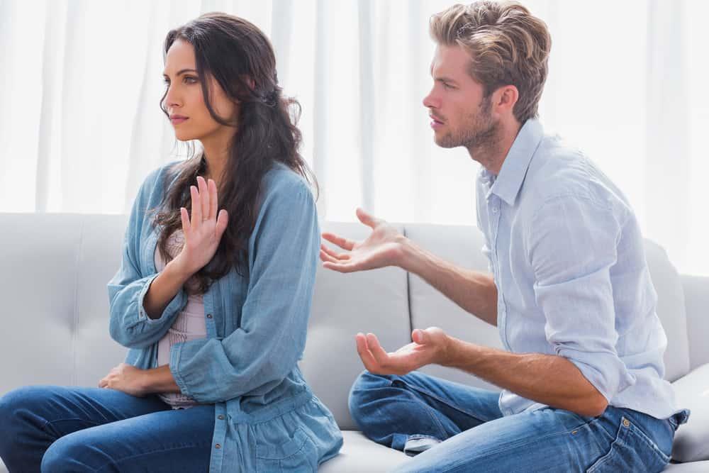 Die Brünette deutet mit der Hand auf ihren Mann, dass es genug ist