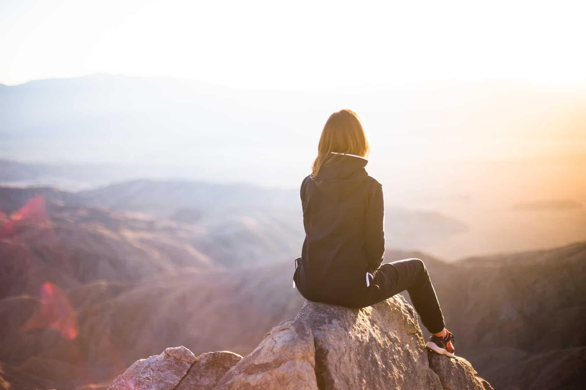 Die Frau sitzt mit dem Rücken gedreht auf einem Stein