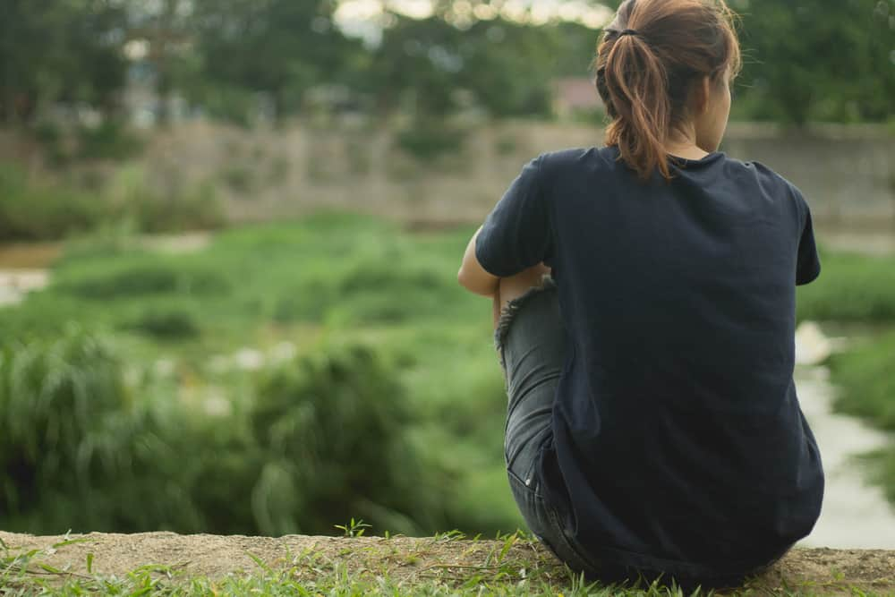 Die Frau sitzt mit dem Rücken zum Boden