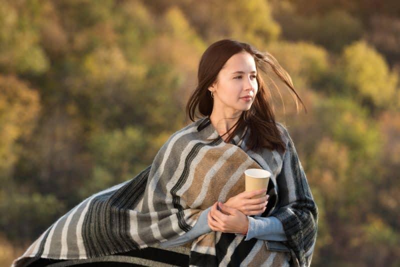 Draußen steht eine Brünette in einer bunten Pashmina mit einem heißen Getränk in der Hand