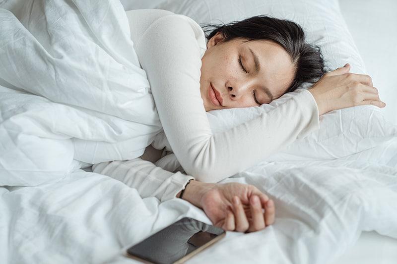 eine Frau, die in einem Bett mit weißen Laken schläft