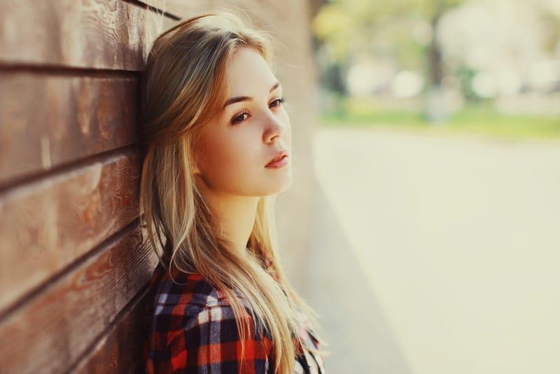 Draußen an einer Holzwand gelehnt steht eine schöne traurige Blondine