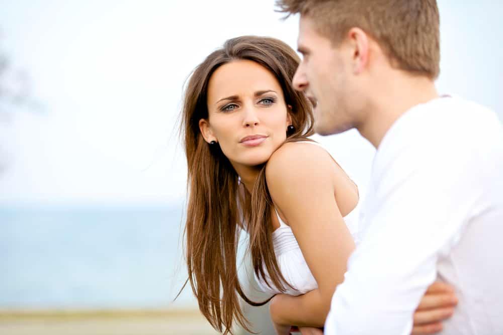 Draußen schaut eine schöne Frau ernsthaft einen Mann an, der ihr etwas erzählt