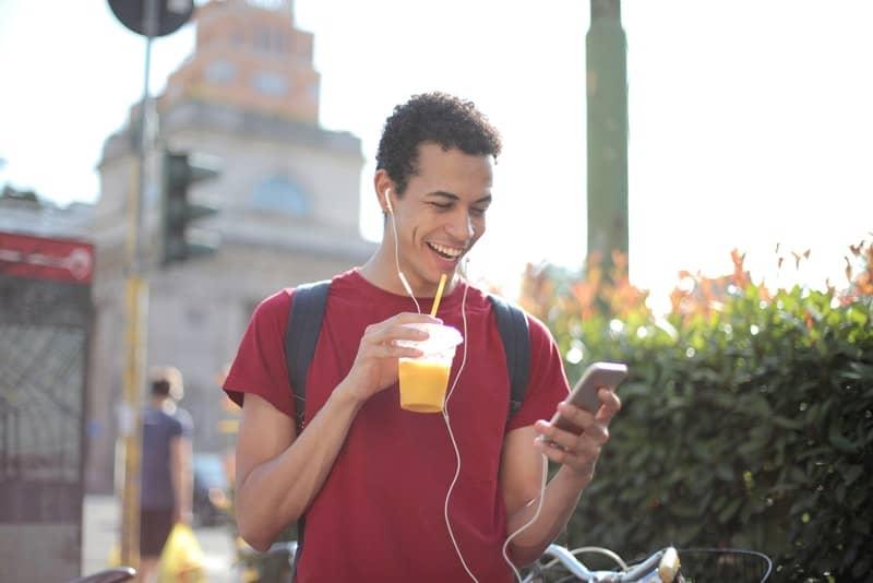 Draußen steht ein lächelnder Mann in einem roten T-Shirt und schaut sich etwas auf seinem Handy an