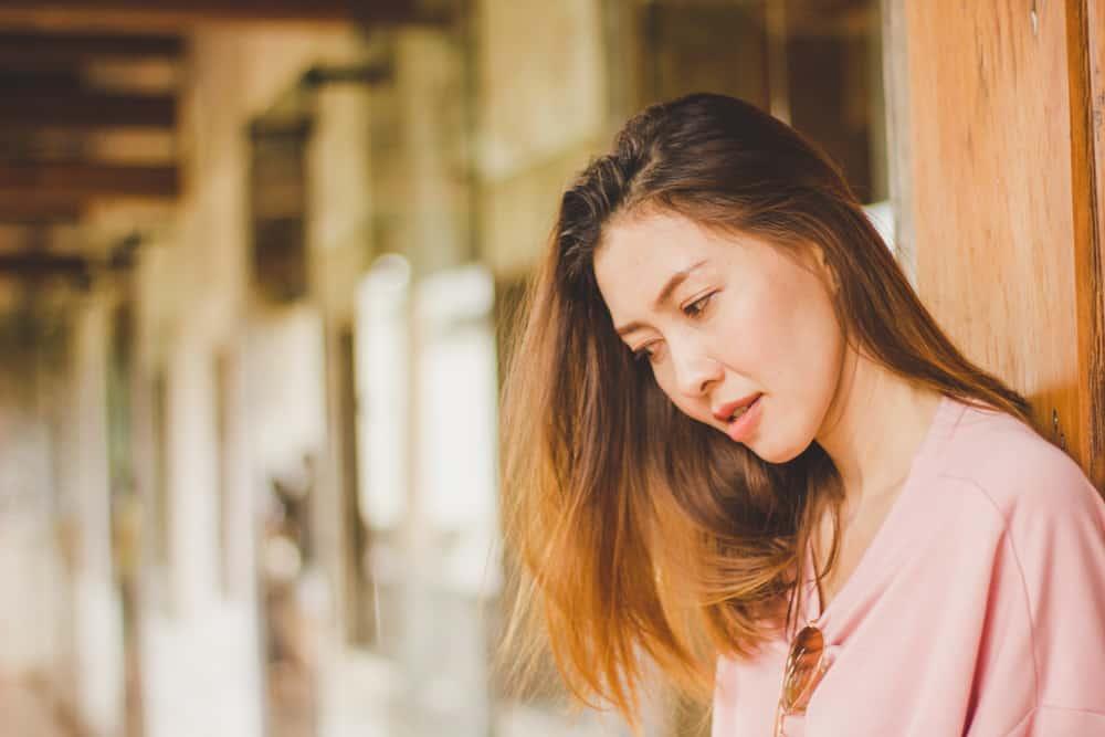 Draußen steht eine enttäuschte Chinesin in einem rosa T-Shirt und denkt nach