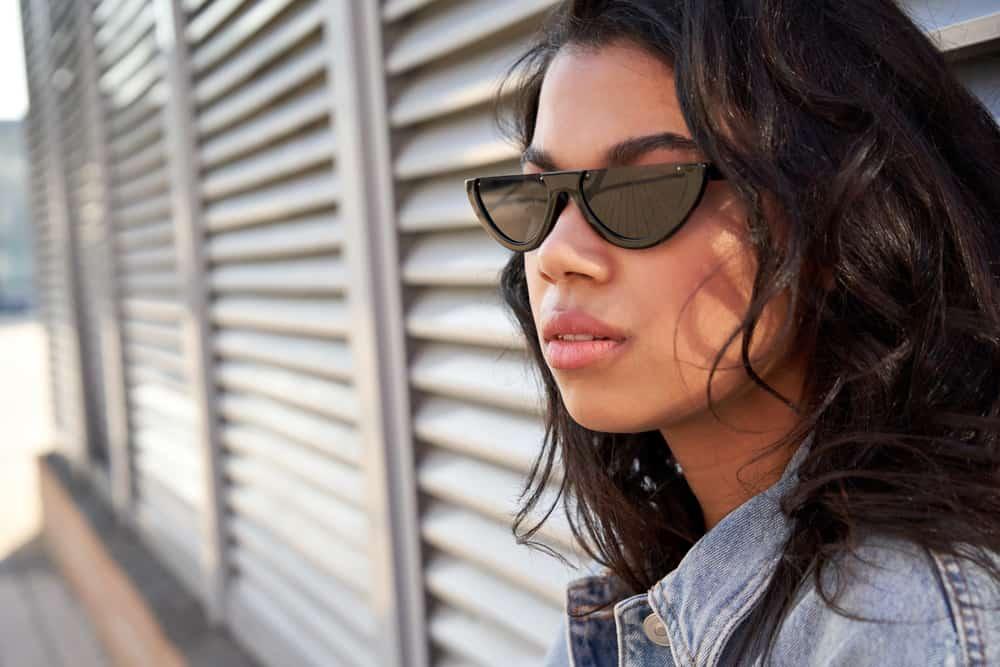 Draußen steht eine ernsthafte Brünette mit Sonnenbrille