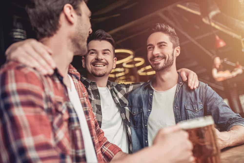 Drei lächelnde Männer trinken Bier an der Bar