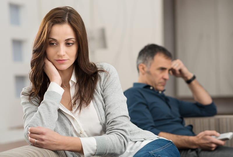 eine nachdenkliche Frau, die auf der Couch sitzt, während ihr Mann fernsieht