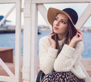 Auf dem Pier neben dem Zaun sitzt eine nachdenkliche traurige Frau mit einem Hut auf dem Kopf