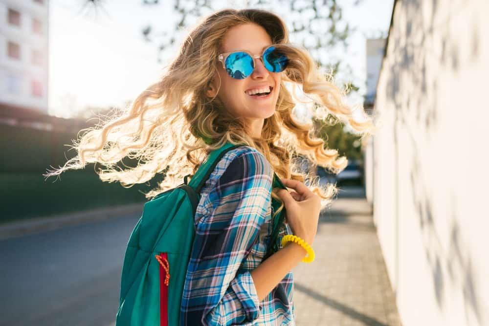 Dünne lächelnde Blondinen mit Sonnenbrille gehen die Straße entlang