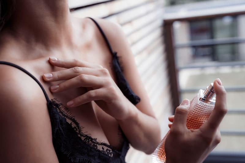 Ein Mädchen in einem schwarzen Unterhemd zieht Parfüm an