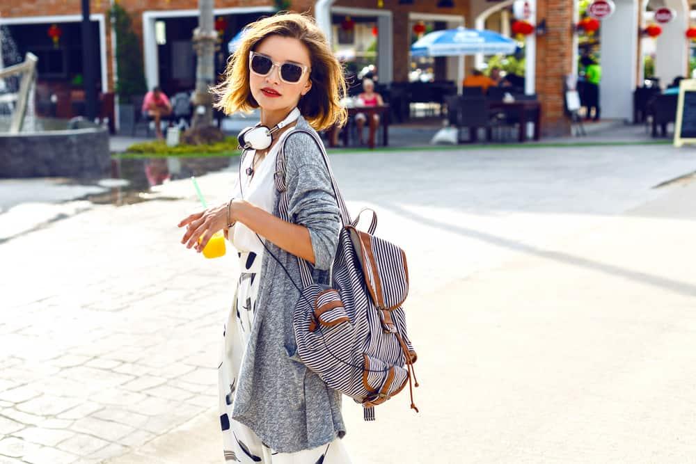 Ein Mädchen mit Sonnenbrille und Saft in der Hand geht durch die Stadt