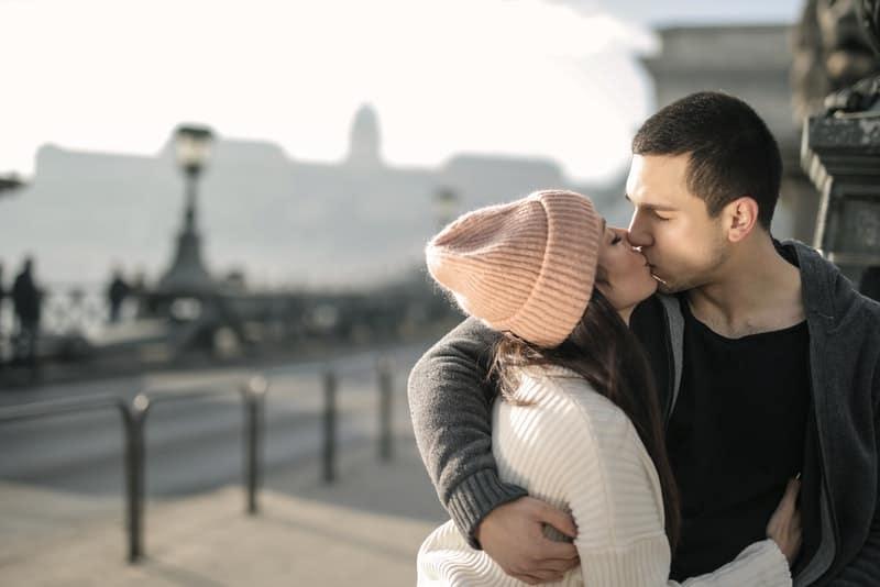 Ein Mädchen und ein Mann küssen sich auf der Straße