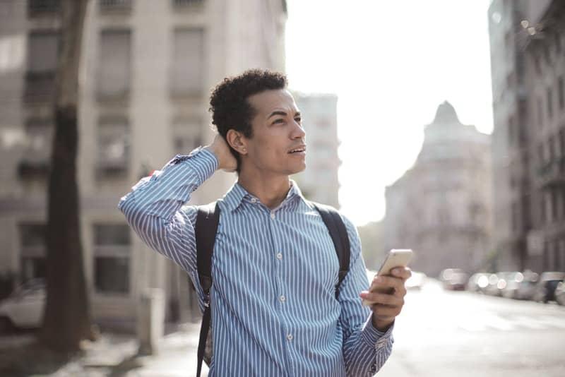 Ein Mann auf der Straße mit einem Telefon in der Hand steht auf und denkt nach