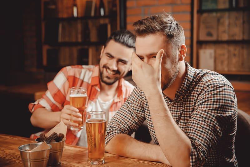 Ein Mann berührt seinen Kopf, während er mit einem Freund in einer Bar lacht