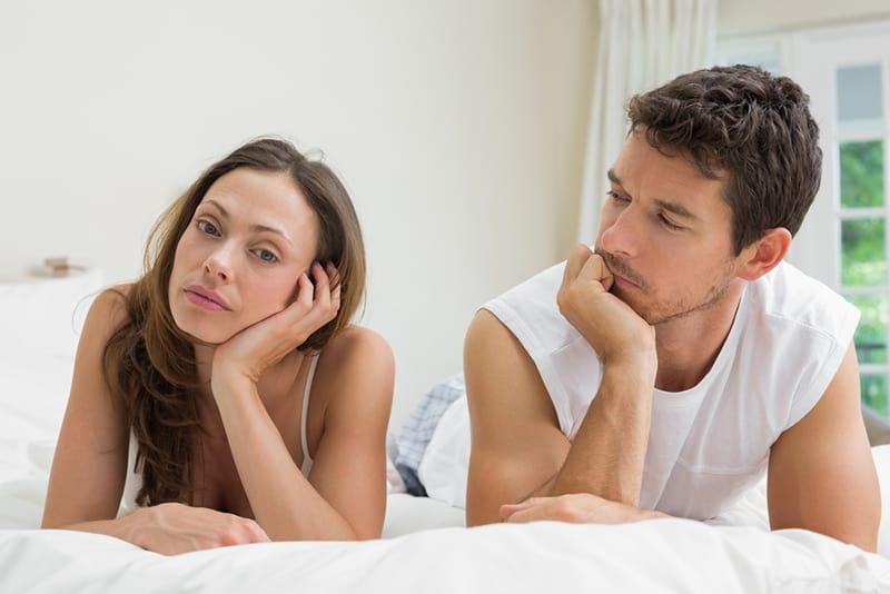 Ein Mann, der seine ernsthafte Freundin ansieht, während beide auf dem Bett liegen