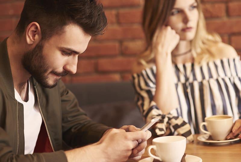 Ein Mann, der während eines Dates mit seiner Freundin im Café ein Smartphone benutzt