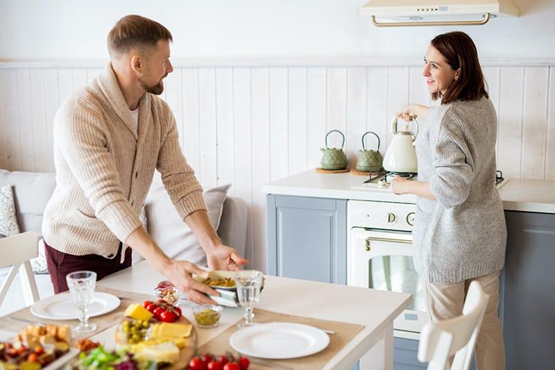 Ein Mann hilft einer Frau, Essen für das Mittagessen zu servieren