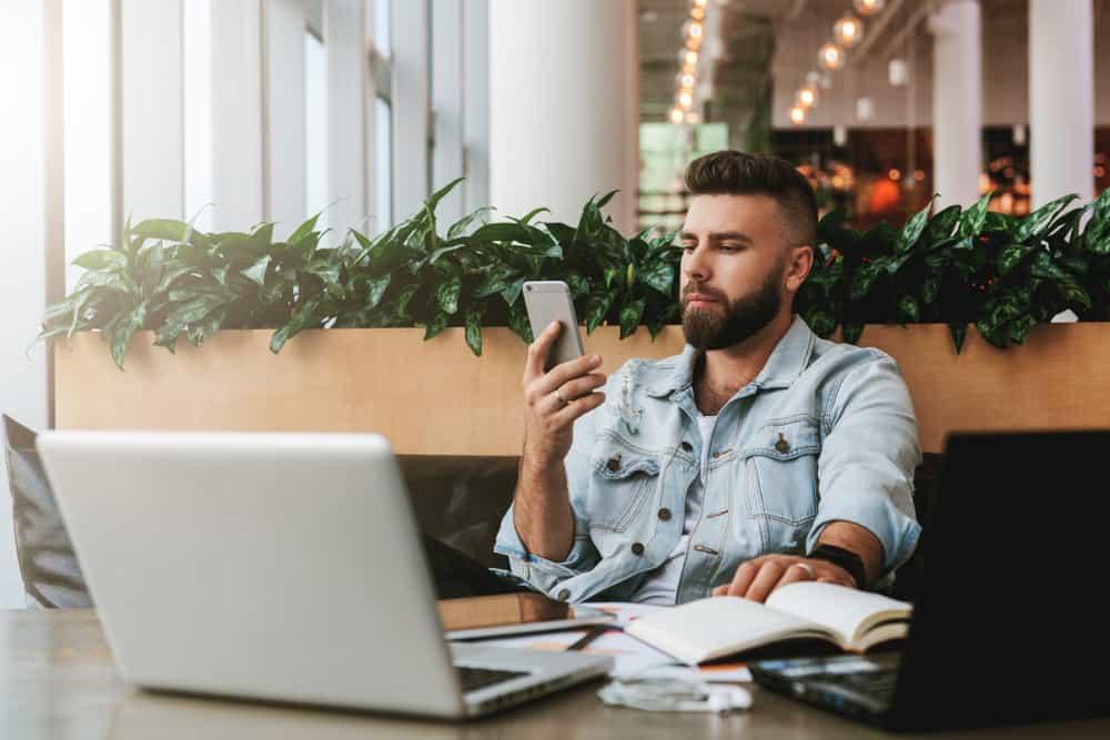 Ein Mann in einem Jeanshemd schaut ernsthaft auf sein Handy