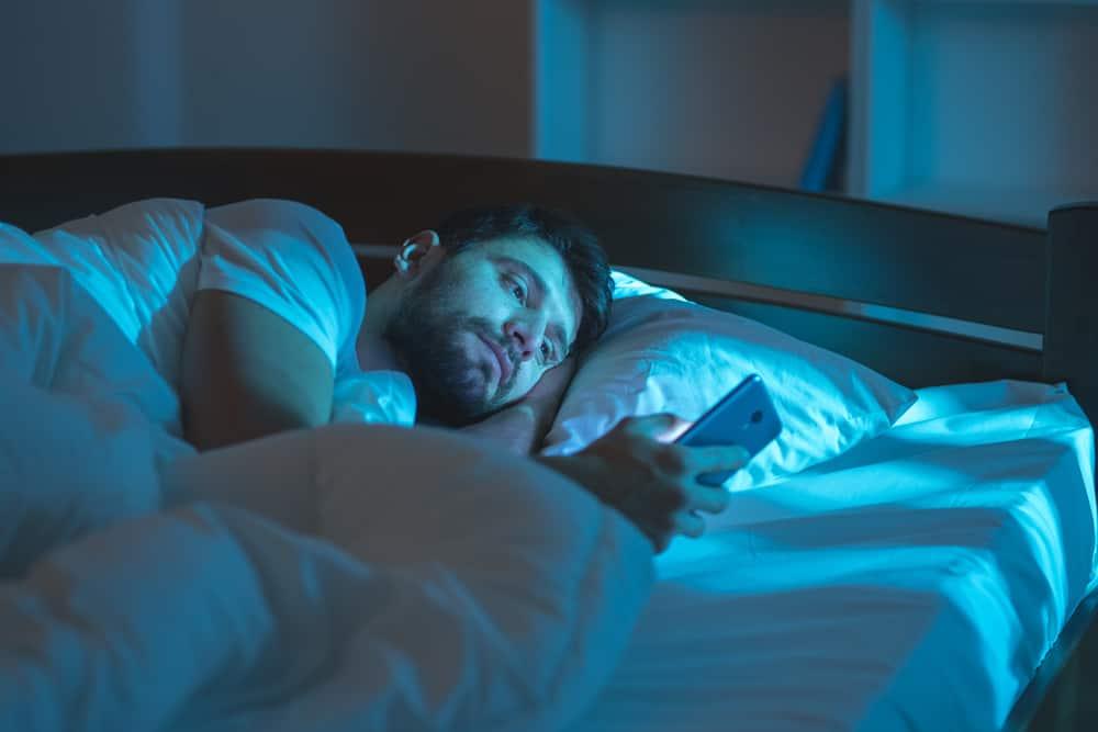 Ein Mann liegt im Bett und benutzt ein Smartphone