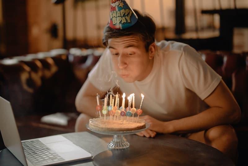 Ein Mann löscht Kerzen auf einer Geburtstagstorte