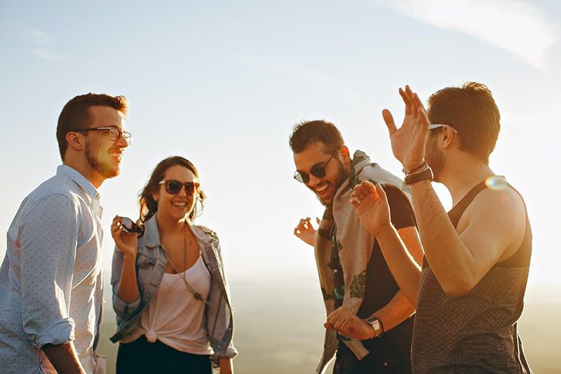 Ein Mann mit Brille steht, während seine Freunde tagsüber draußen um ihn herum tanzen
