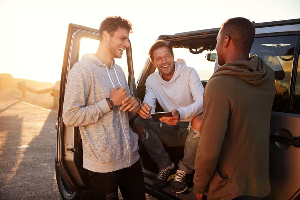 Ein Mann mit Freunden steht am Auto und lacht