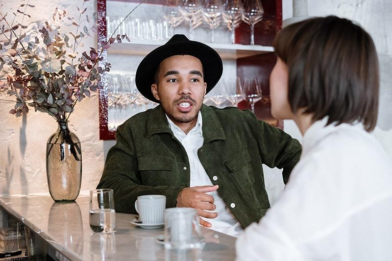 Ein Mann mit Hut spricht mit einer Frau bei einem Date im Café
