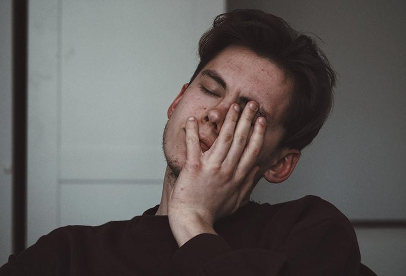 Ein Mann mit geschlossenen Augen fühlte sich deprimiert und berührte sein Gesicht mit der Handfläche