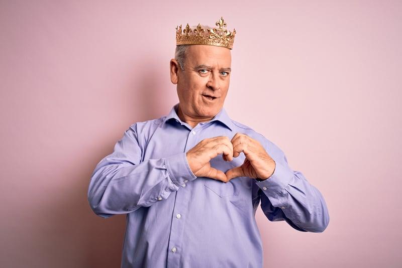 Ein Mann mittleren Alters, der die goldene Krone des Königs trägt und mit den Händen ein Herzsymbol macht