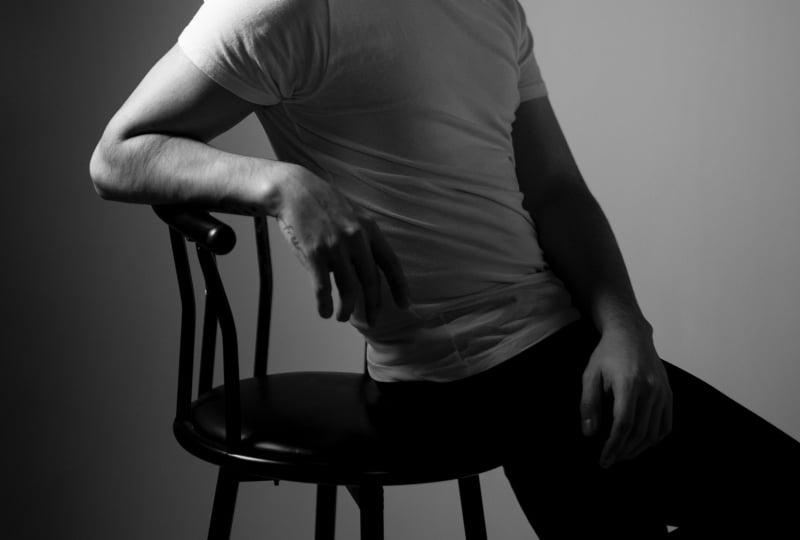 Ein Mann sitzt auf einer Stuhlkante