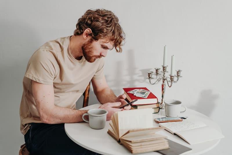 Ein Mann sitzt und schreibt eine SMS