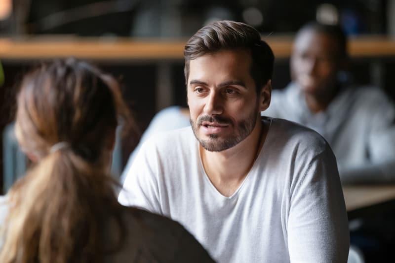 Ein Mann spricht mit einer Frau, während er im Café sitzt