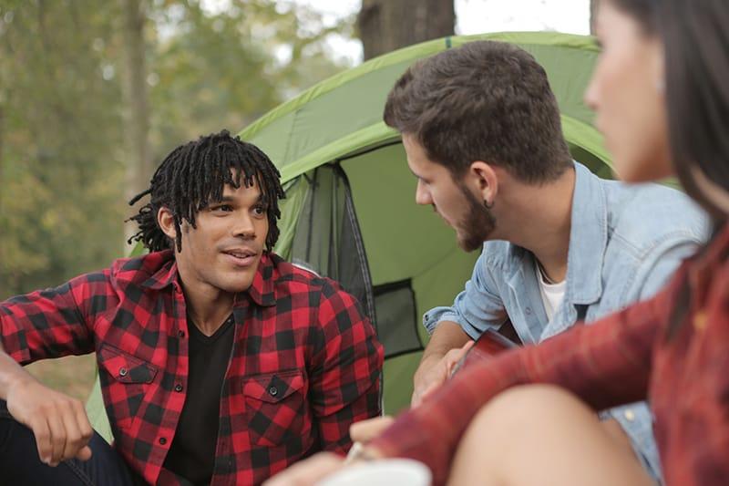 Ein Mann spricht mit seinen Freunden, während er vor dem Zelt sitzt