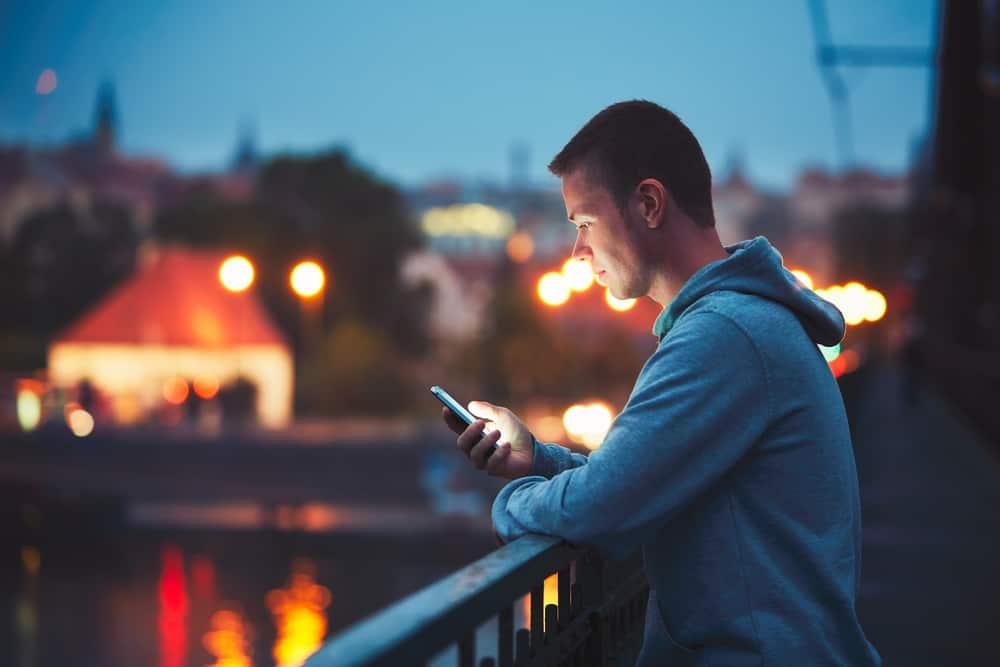 Ein Mann stand mit einem Telefon in der Hand auf dem Balkon