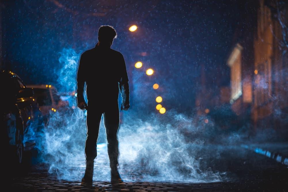 Ein Mann steht im Dunkeln auf der Straße