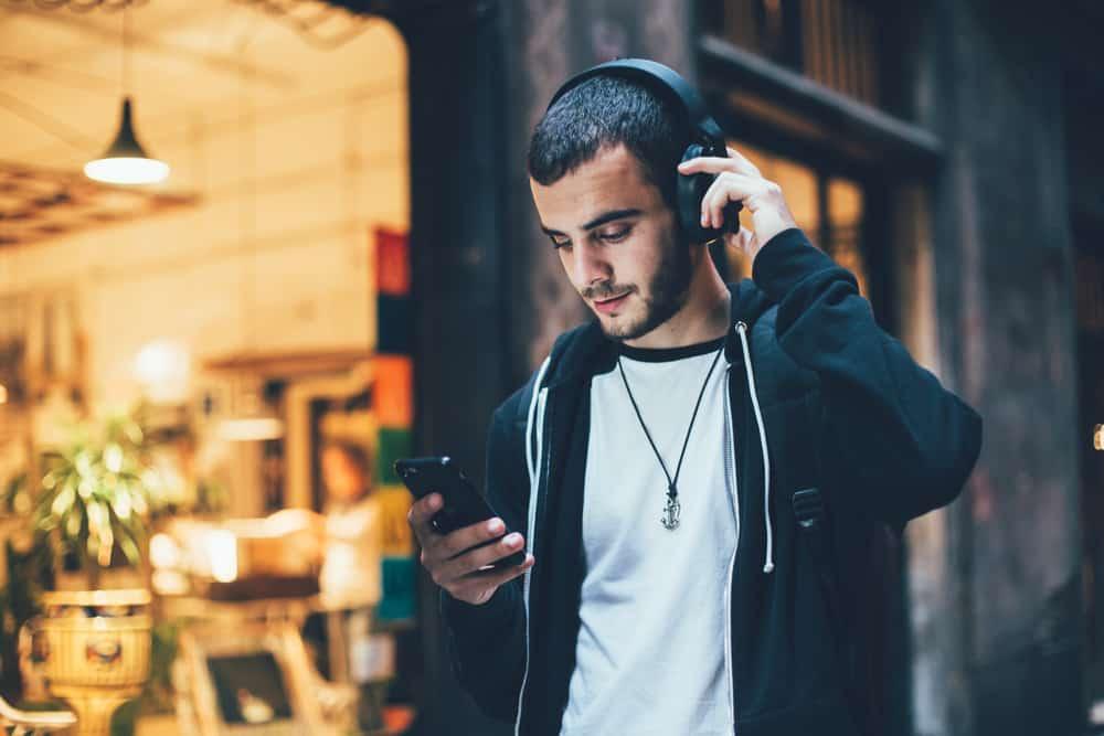 Ein Mann steht mit Kopfhörern draußen und benutzt ein Smartphone