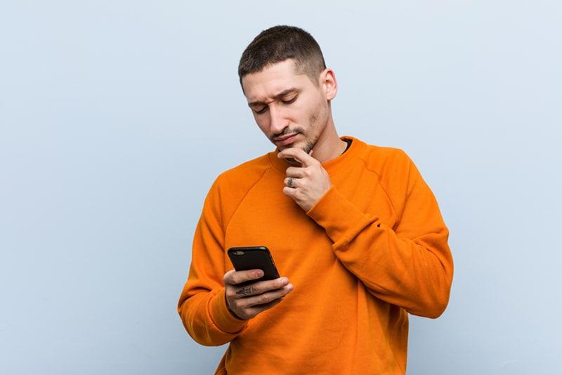 ein Mann, der ein orangefarbenes Sweatshirt trägt, ein Telefon hält und es mit einem zweifelhaften und skeptischen Ausdruck betrachtet