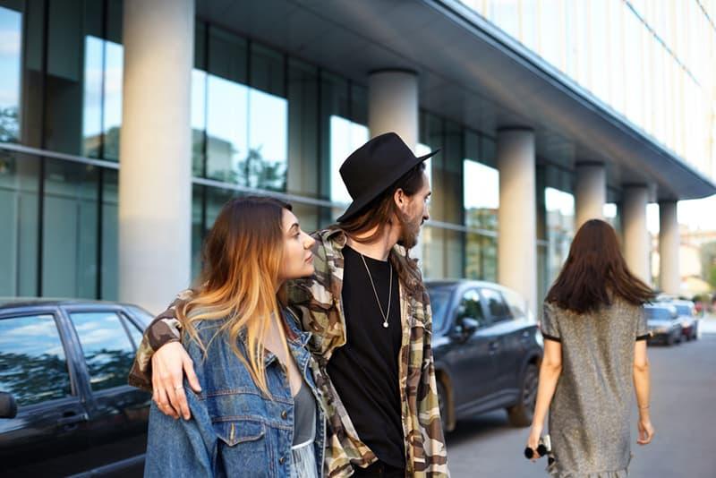 Ein Mann umarmt seine Freundin auf der Straße und schaut einer anderen Frau nach