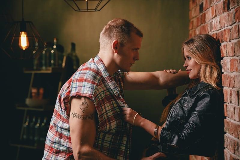 Ein Mann und eine Frau flirten im Café, während sie sich an die Wand lehnten