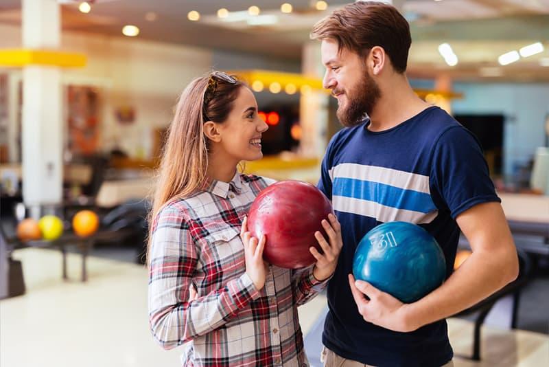 Ein Mann und eine Frau halten Bowlingkugeln, während sie lächeln und sich ansehen