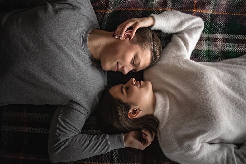 Ein Mann und eine Frau liegen auf dem Bett und sehen sich an