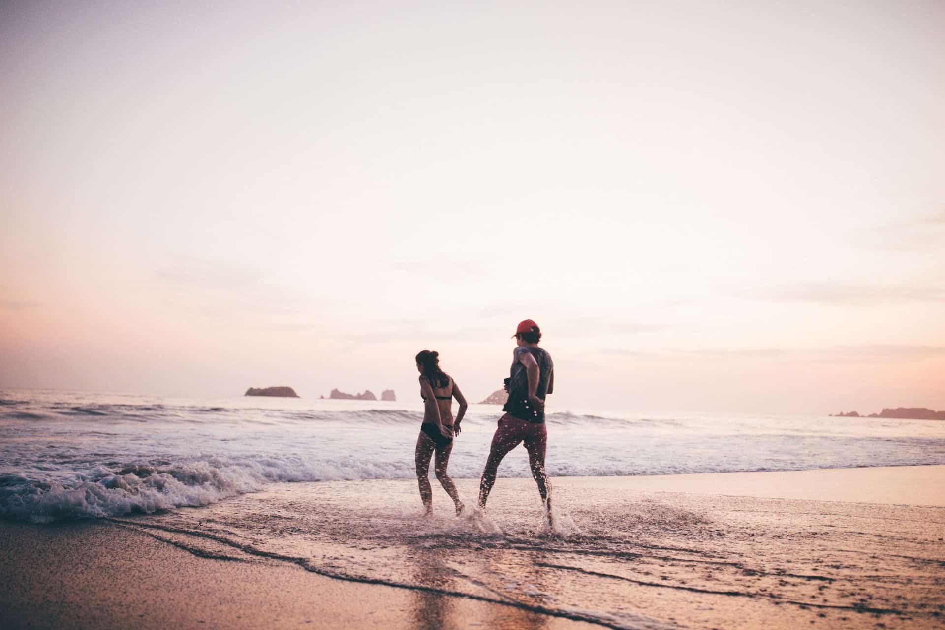 Ein Mann und eine Frau rennen über den Strand